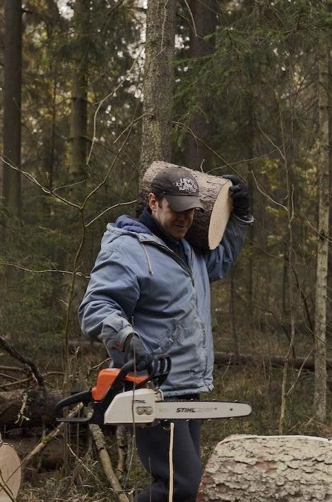 Hombre que trabaja con la madera y la sierra electrica